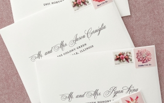 Wedding invitation envelopes with guest address envelope printing and a mix of regular and vintage postage.