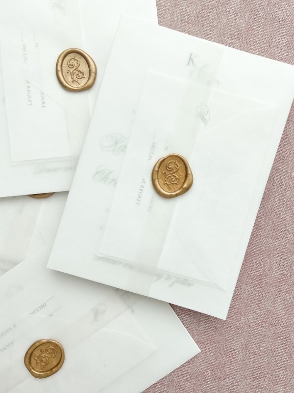 Wedding invitation with translucent vellum wrapped closed with a gold oval wax seal sticker.